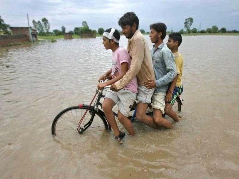 Men ride on a bicycle through a flooded road after a heavy downpour on the outskirts of Jammu.