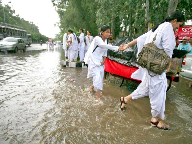 College girls wade through a flooded road after a heavy downpour in Jammu.