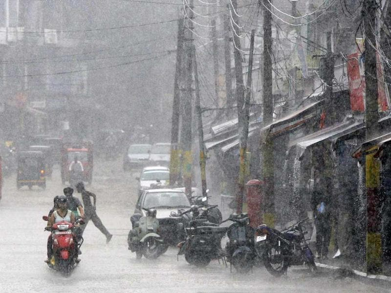 People ride a scooter through a road during a heavy downpour in Jammu.