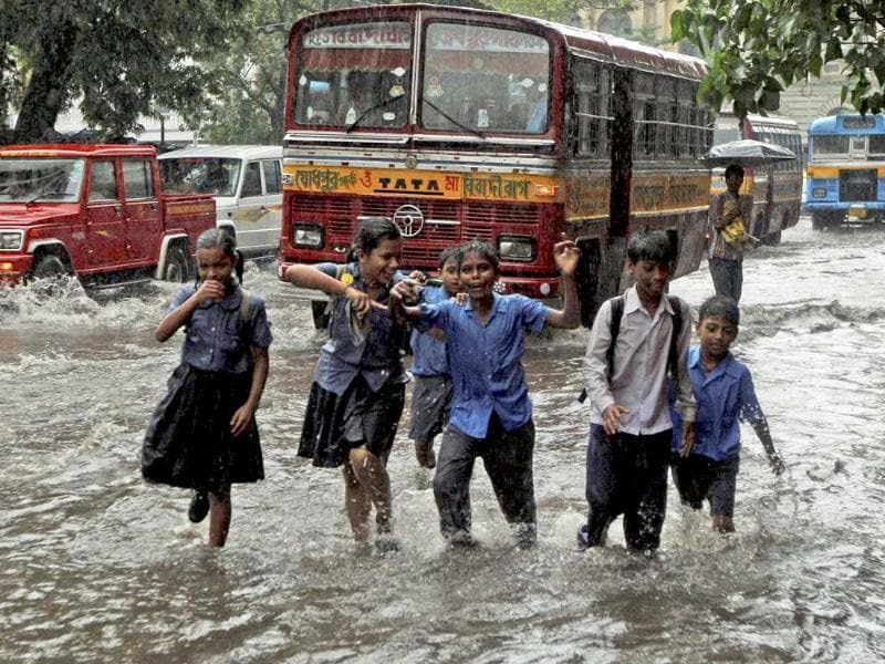 School students play on a waterlogged road as they return from school in Kolkata after heavy rain.