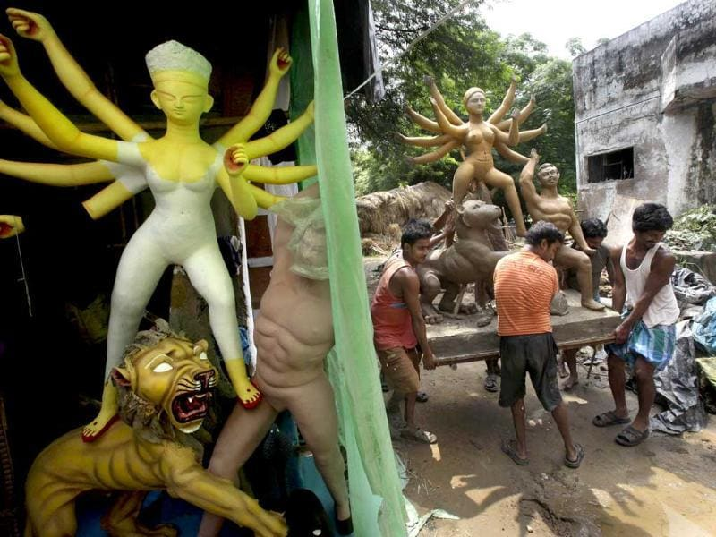 Artisans carry an idol of Goddess Durga to dry in the sun, ahead of the Durga Puja festival in New Delhi.