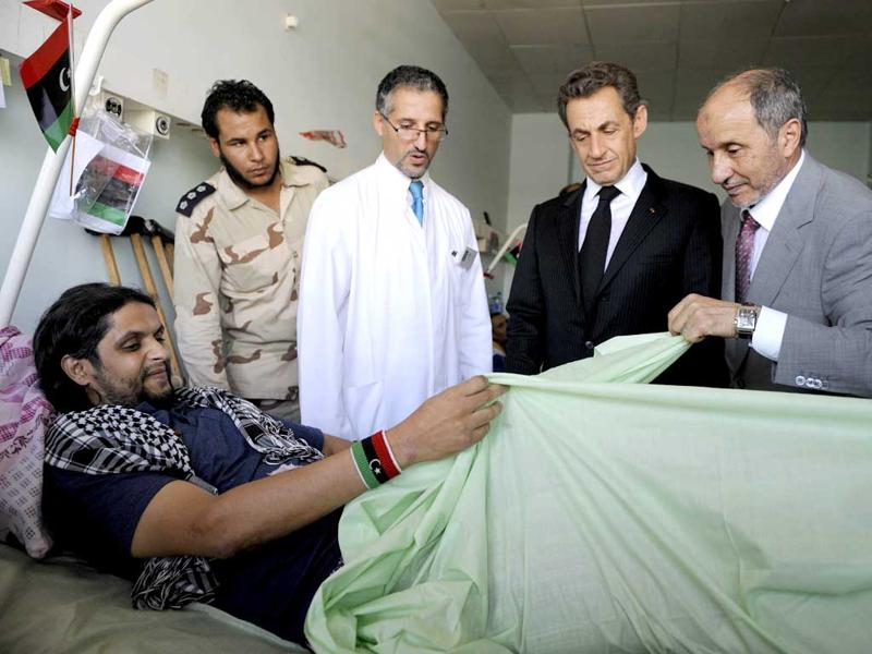 French President Nicolas Sarkozy (C) and National Transition Council President Mustafa Mohammed Abdul Jalil (R) visit injured people in the Tripoli Medical center.