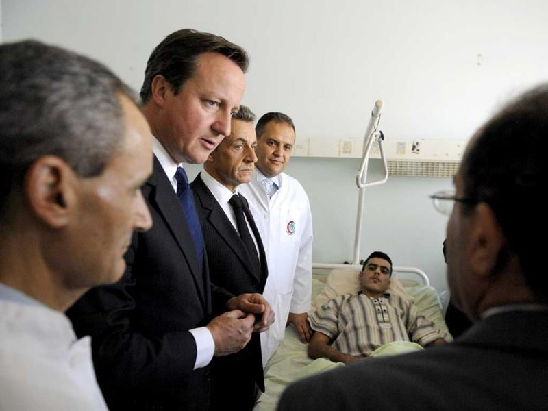 French President Nicolas Sarkozy, Britain's Prime minister David Cameron and National Transition Council Prime minister Mahmud Jibril (R) visit injured people in the Tripoli Medical center during their travel in Libya in Tripoli.