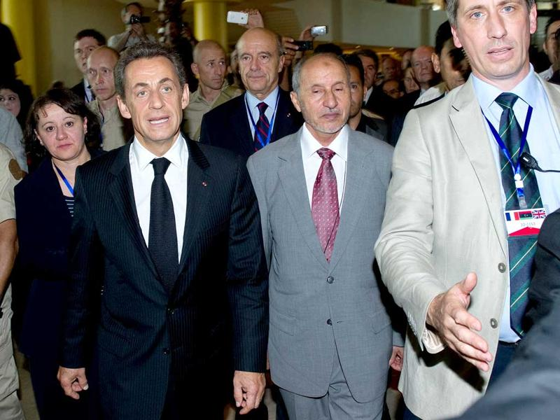 French President Nicolas Sarkozy and President of the National Transitional Council Mustafa Abdul Jalil walk through the lobby of the Corinthia hotel in central Tripoli.