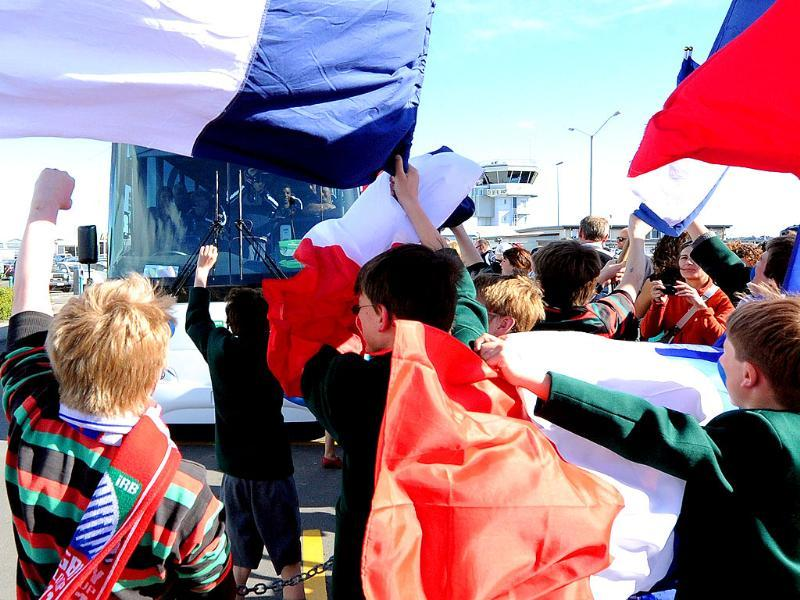 Fans wave flags as the French team take the bus after their arrival at the Hawke's Bay airport in Napier during the 2011 Rugby World Cup.