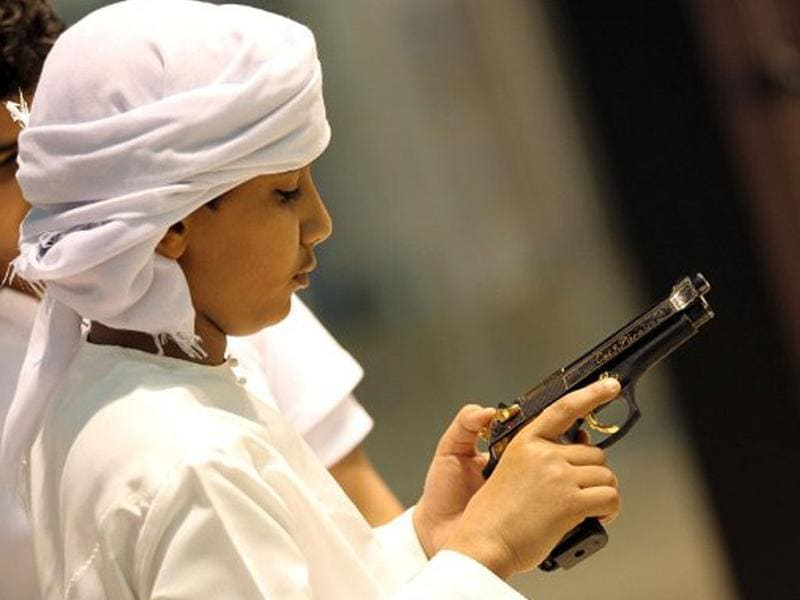 An Emirati boy looks at a hand gun on the first day of 17th Abu Dhabi International Hunting and Equestrian exhibition (ADIHEX).