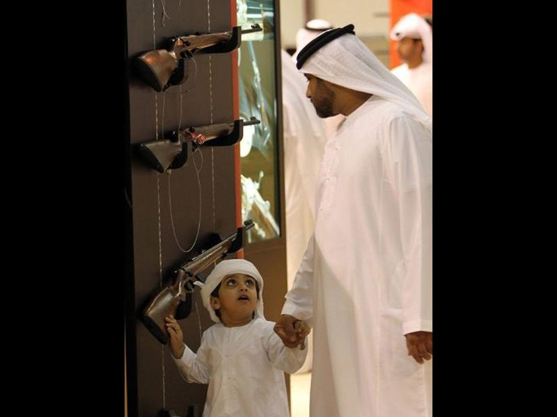 An Emirati boy walks with his father, as they look at the displays on the first day of 17th Abu Dhabi International Hunting and Equestrian exhibition (ADIHEX).