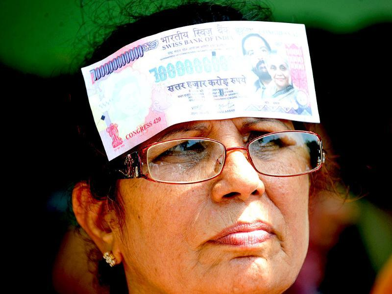 A supporter of the Bharatiya Janata Party (BJP) places a fake Indian bank note on her head, as she protests against petrol price hikes in New Delhi.