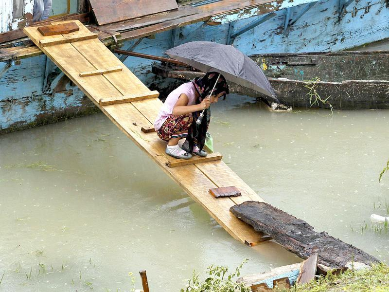 A Kashmiri girl carrying an umbrella crosses a pathway from her houseboat on Jehlum River to shore during rainfall in Srinagar.