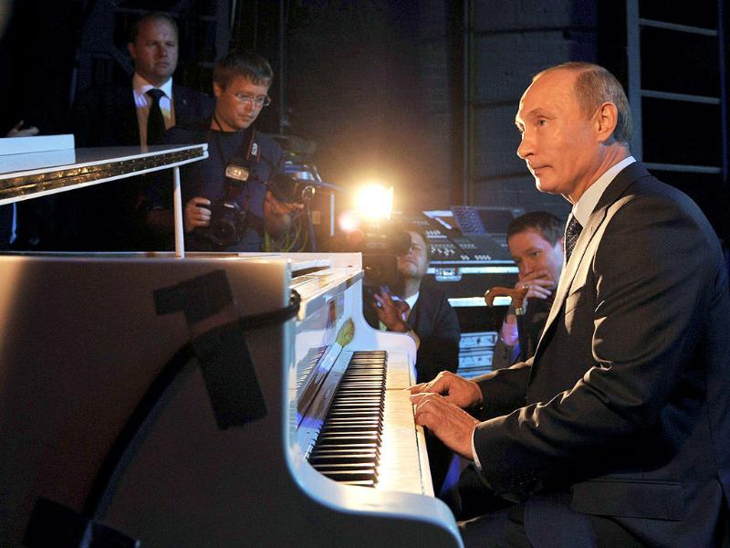 Russia's Prime Minister Vladimir Putin plays the piano while visiting the Theater of Nations in Moscow.
