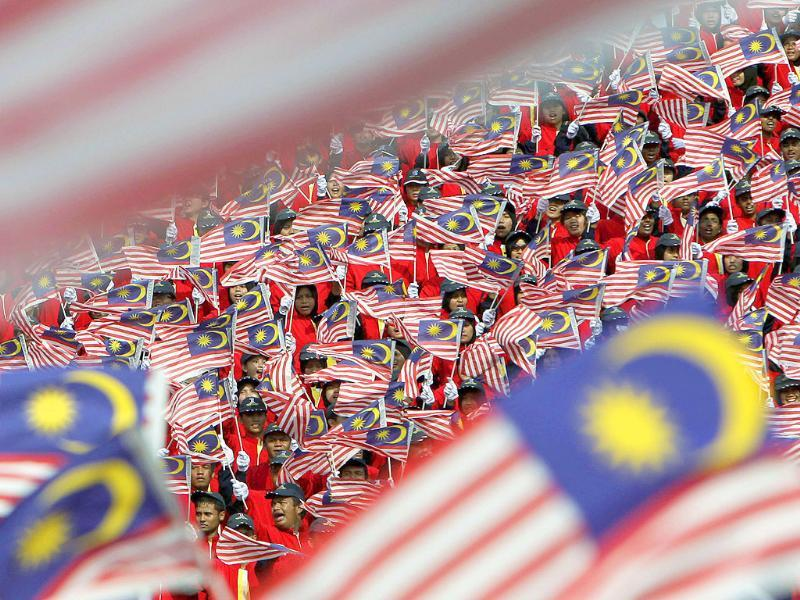 Malaysians wave the national flags during the double celebrations of Malaysia Day and Independence Day in Kuala Lumpur.