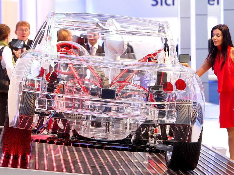 A model stands next to a transparent car showing security components at the 64th Frankfurt Auto Show in Frankfurt, Germany.
