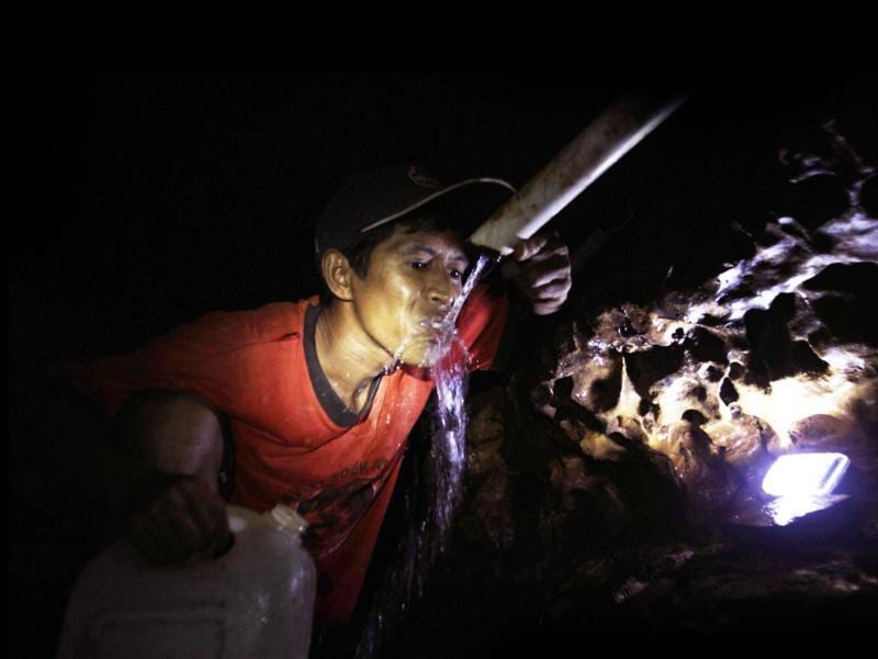 A villager drinks water inside a 75-metres deep cave while collecting clean water at Gedompol village in Pacitan, in Indonesia's East Java province
