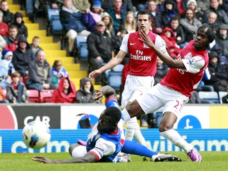 Arsenal's Gervinho, right, beats the tackle of Blackburn's Chris Samba, left, to score a goal during their English Premier League soccer match at Ewood Park, Blackburn, England.
