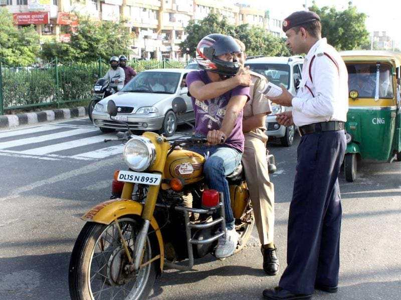 A traffic police personnel warns bike rider for not wearing helmet during 'Road Safety' campaign in New Delhi.