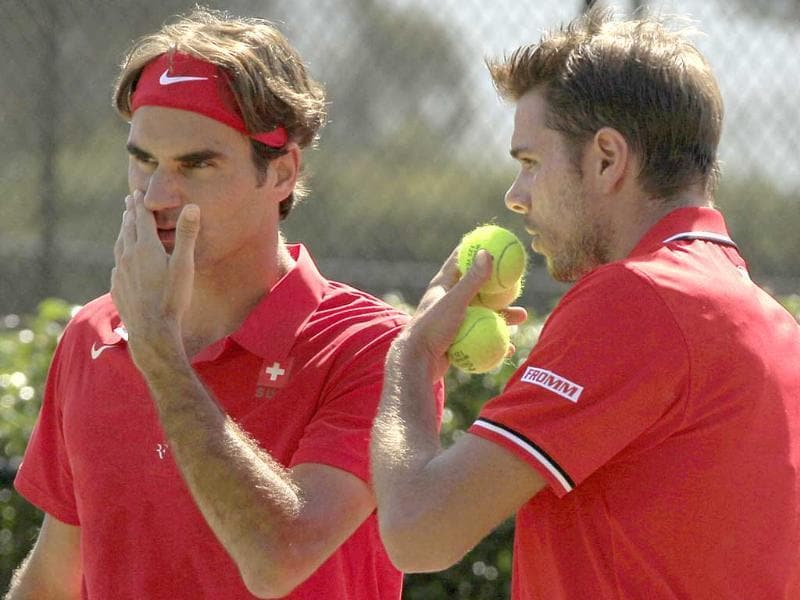 Switzerland's Roger Federer (L) and teammate Stanislas Wawrinka discuss tactics in a play against Australia's Lleyton Hewitt and Chris Guccinone during their doubles tennis match in a Davis Cup world group playoff in Sydney.