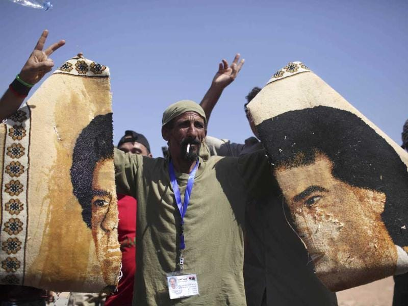 A former rebel fighter holds pieces of a carpet with the image of Muammar Gaddafi at a checkpoint in Wadi Dinar, Libya.