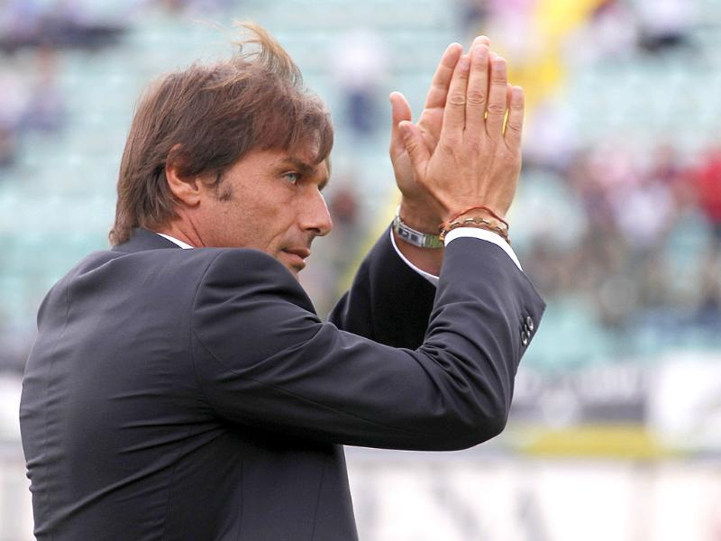 Juventus' coach Antonio Conte arrives on the pitch and cheers his supporters prior of their serie A football match at Artemio Franchi stadium in Siena.