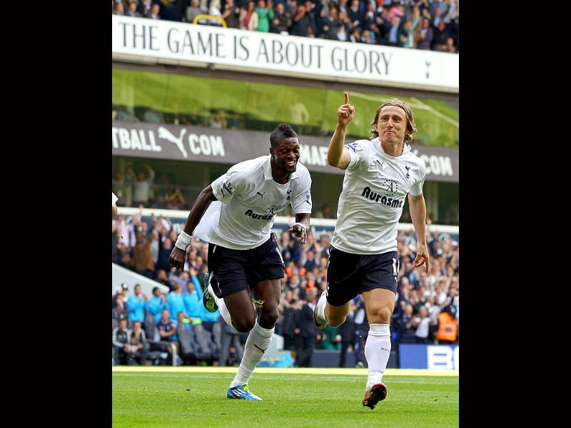 Tottenham Hotspur's midfielder Luka Modric (R) celebrates scoring the opening goal with teammate Emmanuel Adebayor (L) during of the English Premier League football match against Liverpool ain north London, England.