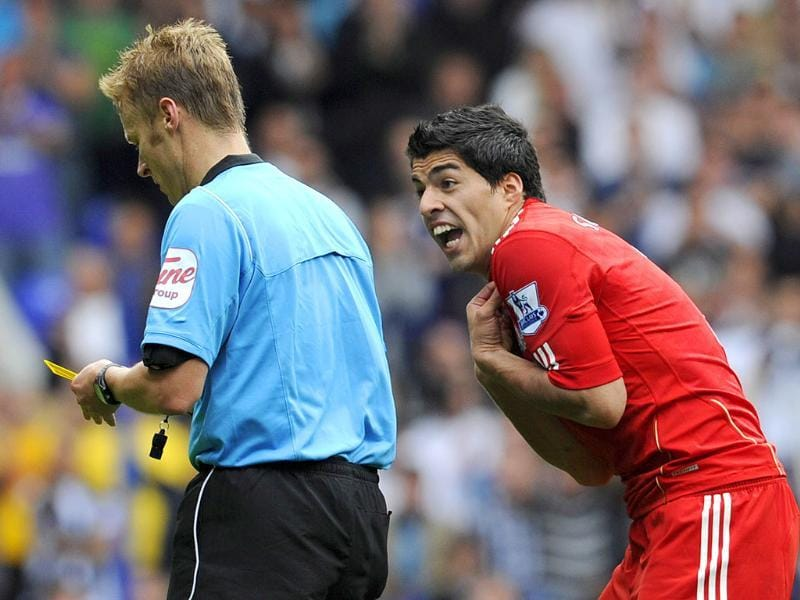 Liverpool's Luis Suarez (R) reacts after referee Mike Jones shows him a yellow card during their English Premier League soccer match against Tottenham Hotspur in London.