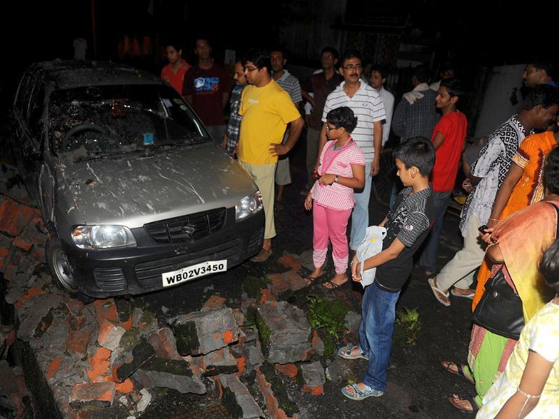Residents gather near a damaged car and wall rubble in Siliguri after an earthquake hit Sikkim.