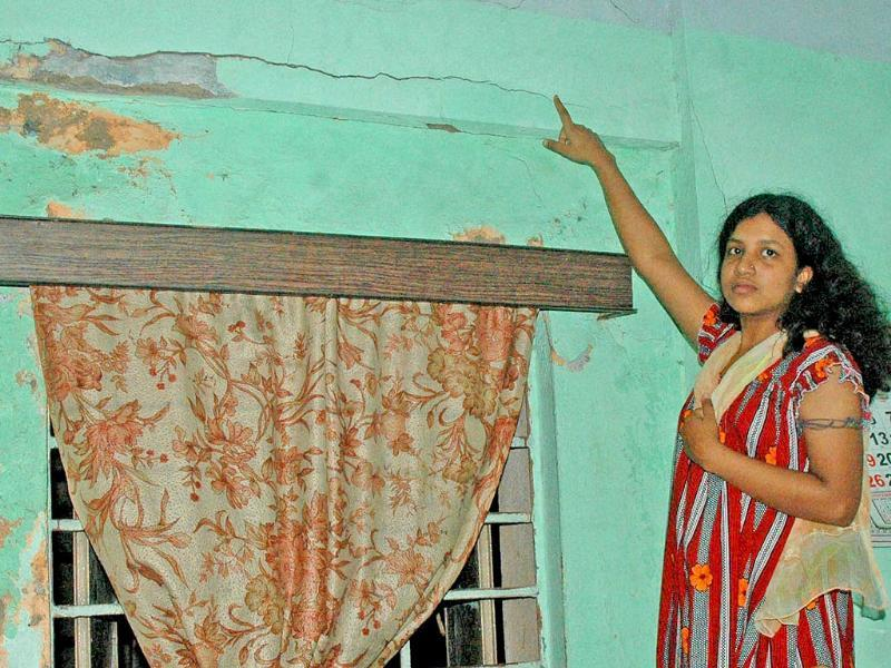 A lady shows crack in her wall after an earthquake occurred in Kolkata.