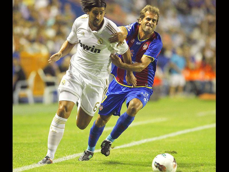 Real Madrid's Sami Khedira (L) and Levante's Jose Barkero fight for the ball during their Spanish first division soccer match at the Ciudad de Valencia Stadium in Valencia.