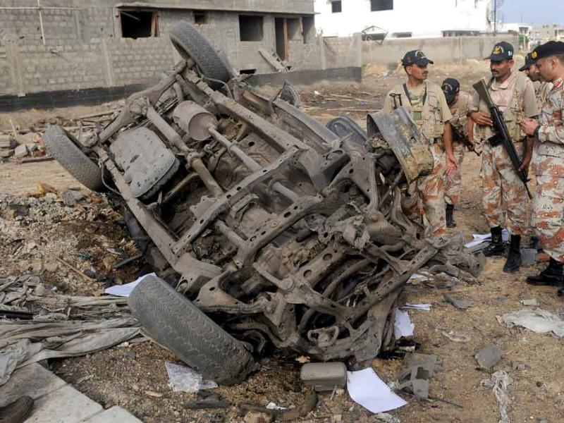 Pakistani paramilitary soldiers inspect a destroyed vehicle after a car bomb blast in Karachi.