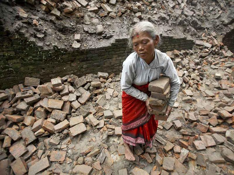 Subhadra Pathi, 70, collects bricks outside her house a day after a magnitude 6.8 earthquake hits Bhaktapur, Nepal.
