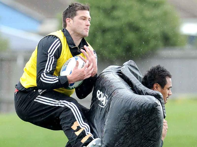 New Zealand All Black player Cory Jane (L) catches the ball as teammate Isaia Toeava (R) carries the padding during a training session in Christchurch.