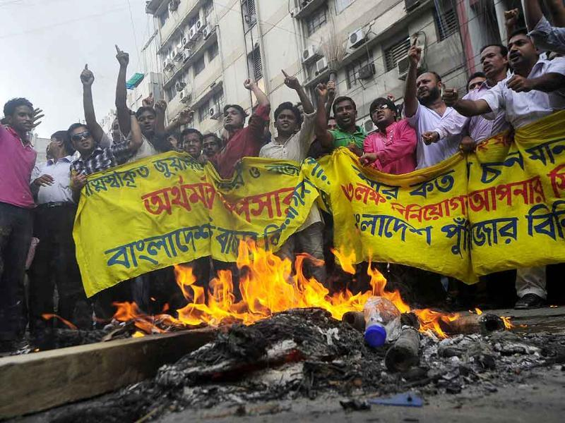 Bangladeshi investors light a fire and shout slogans in the commercial heart of the Bangladeshi capital Dhaka.
