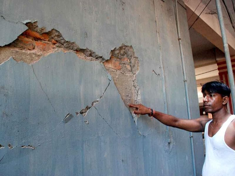 A man shows cracks in a building after last night's earthquake in Guwahati.