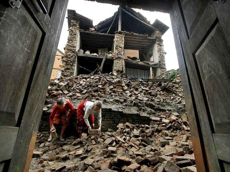 Nepalese women remove bricks of the damaged house to make way for pedestrians after an earthquake of magnitude 6.9 shook northeastern India and Nepal.