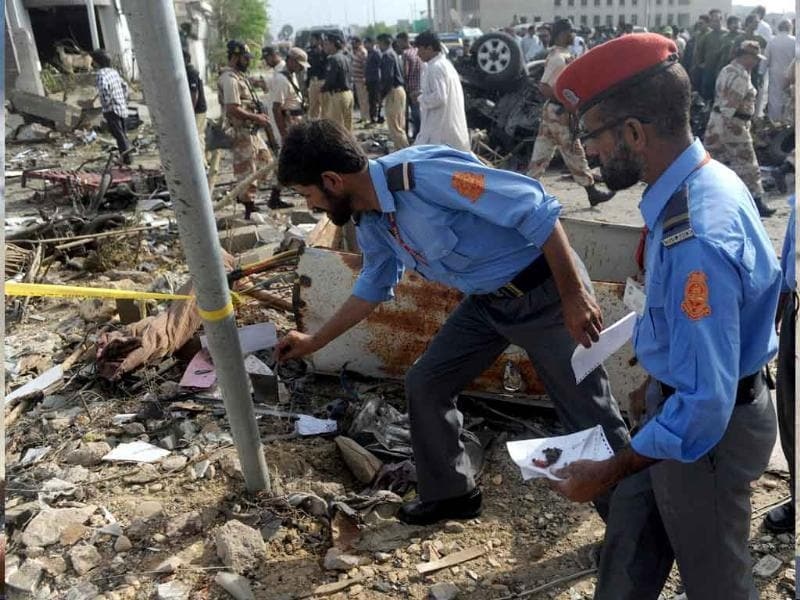 Pakistani investigators inspect the site of a car bomb blast in Karachi.