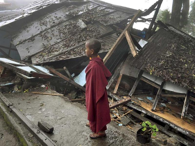 A young Buddhist monk looks on at a monastery damaged by Sunday's earthquake in Gangtok.