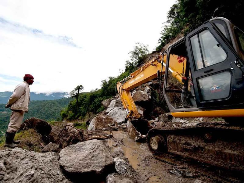 A villager looks on as Indian Border Roads Organisation (BRO) personnel use a digger to clear a landslide at Phengla on the outskirts of Gangtok.
