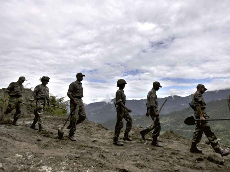 Indian Army personnel walk as they carry spades and other equipments to clear a landslide caused by Sunday's earthquake in Phengla town, Gangtok.