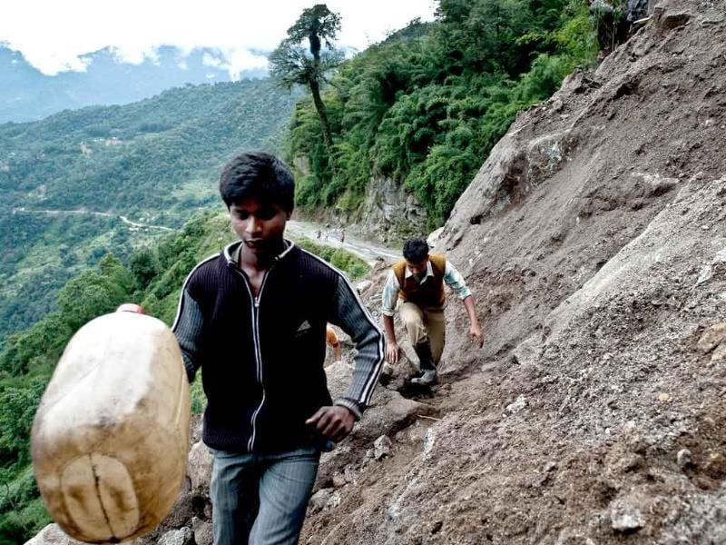 Indian residents carry a jerry-can as they cross a landslide at Phengla on the outskirts of Gangtok.