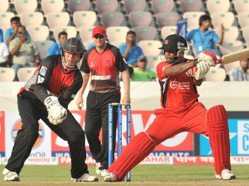 Trinidad and Tobago batsman Adrian Bharath (R) plays a shot as Leicestershire Foxes wicketkeeper Paul Nixon looks on during the Champions League Twenty20 League qualifying pool match between Trinidad and Tobago and Leicestershire Foxes at the Rajiv Gandhi International Stadium in Hyderabad.