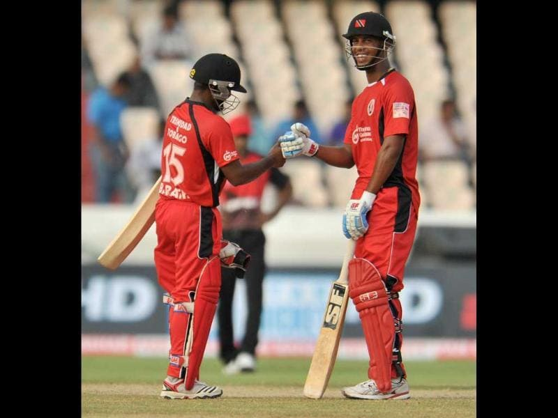 Trinidad and Tobago batsman Adrian Bharath (L) celebrates with teammate Lendl Simmons after scoring a half-century during the Champions League Twenty20 League qualifying pool match between Trinidad and Tobago and Leicestershire Foxes at the Rajiv Gandhi International Stadium in Hyderabad.
