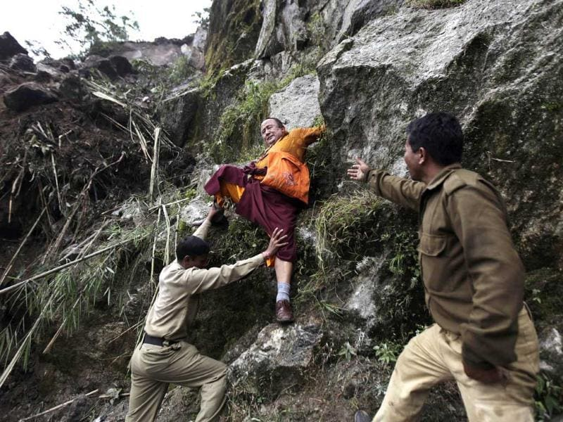 Members of the Indian Army's engineering wing help a Buddhist monk descend a huge landslide following Sunday's 6.8 magnitude earthquake, in Sikkim. Thousands of homeless villagers in the Himalayas spent a miserable night outdoors in heavy rains after a powerful earthquake flattened houses and rescuers struggled to reach victims in the mountains of India, Nepal and Tibet.