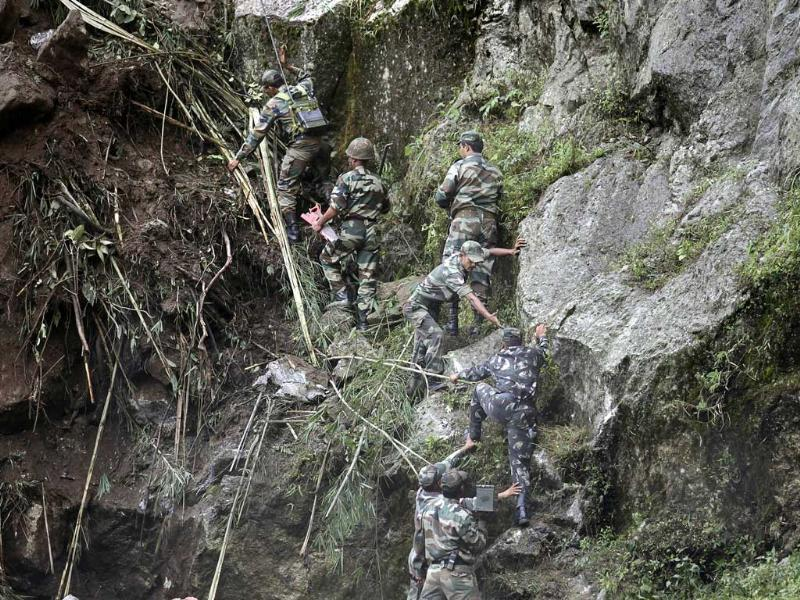 Indian Army personnel help each other as they climb a landslide caused by Sunday's 6.8-magnitude earthquake. Troops trying to reach survivors are pushing through landslide debris with earthmovers after the Himalayan earthquake that shook northeastern India, Nepal and China.
