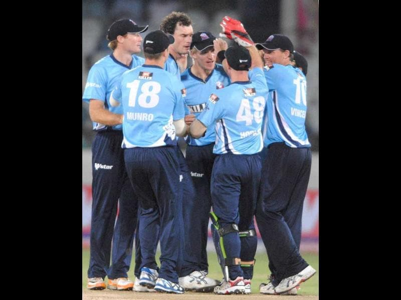 Auckland bowler Kyle Mills, centre, celebrates with his teammates the wicket of Somerset player Chris Jones during the Champions League Twenty20 cricket qualifying match between Somerset and Auckland in Hyderabad.