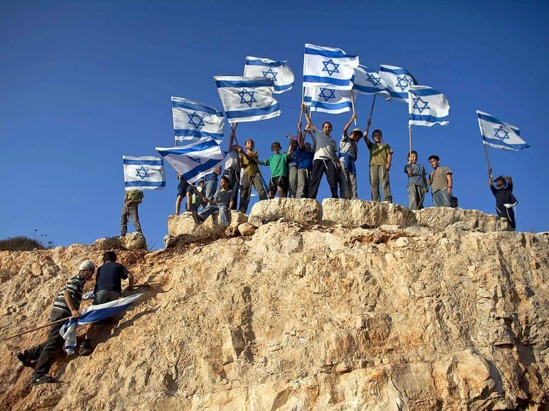 Jewish youth hold Israeli flags at the beginning of a rally march in the West Bank settlement of Itamar, near Nablus.