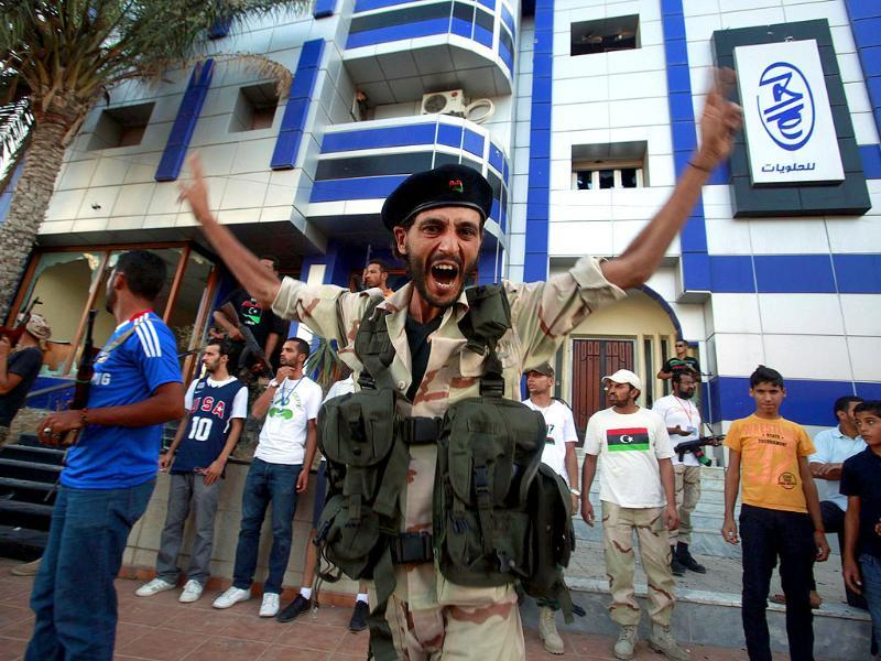 An anti-Gaddafi fighter shouts and gestures in front of a house believed to belong to a Gaddafi loyalist in Tripoli.