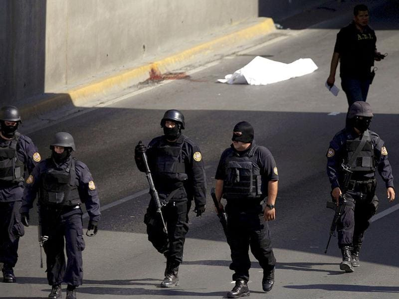 State policemen leave a crime scene where a man was killed in Monterrey.