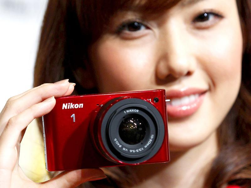 A model poses with Nikon Corp's new Nikon 1 J1 camera, its first lightweight mirrorless interchangeable lens version, at its unveiling ceremony in Tokyo.