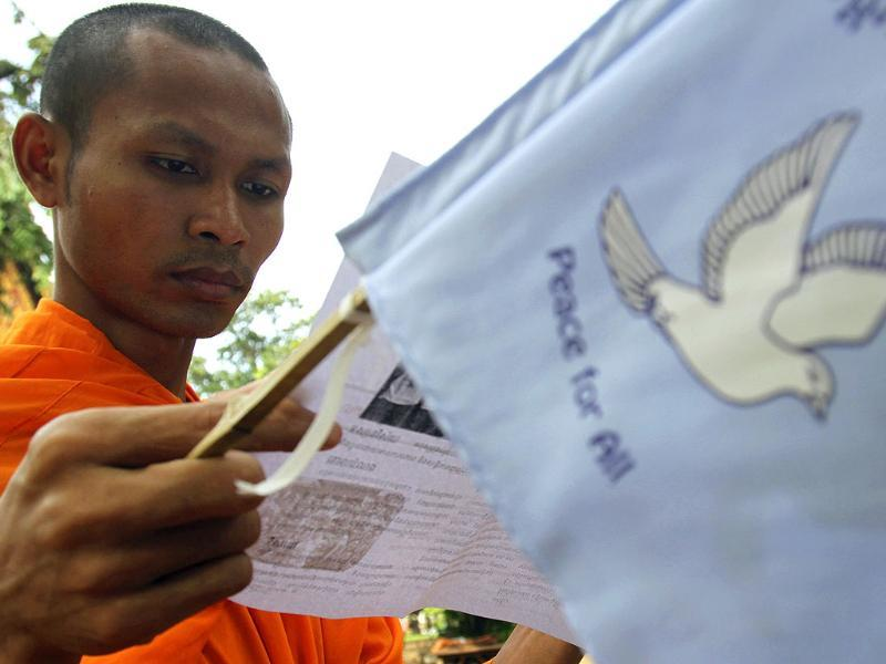 A Buddhist monk reads a document as he attends an event commemorating the International Day of Peace at Wat Phnom pagoda in central Phnom Penh.