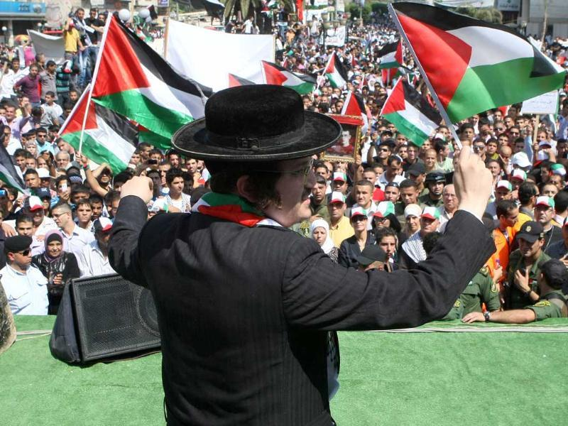 A member of Neturei Karta, a small faction of ultra-Orthodox Jews who oppose Israel's existence, waves Palestinian flags to express their support for the UN membership bid as thousands of Palestinians attend a demonstration in support the Palestinian bid for statehood recognition at the United Nations in the West Bank city of Nablus.