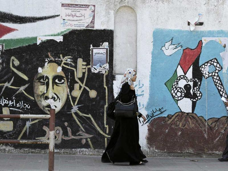 Palestinians walk past murals in Gaza City. Palestinian President Mahmoud Abbas plans on Friday to submit an application for full UN membership for the state of Palestine based in the West Bank, East Jerusalem and the coastal Gaza Strip -- lands occupied by Israel in 1967.